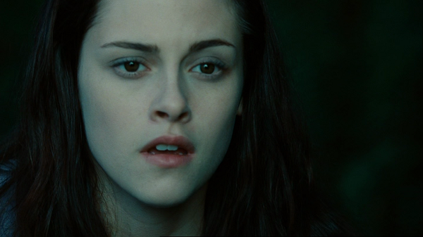 A close-up shot of Bella's open-mouthed face against a blurred green background.