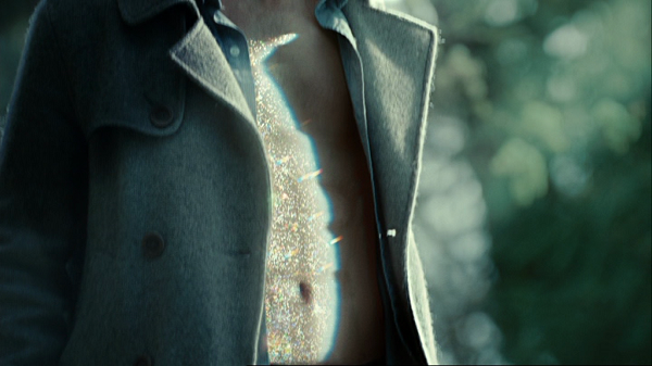 Figure5, A close-up shot showing Edward's torso from his waist to just below his neck. His shirt and jacket are open and the light is reflecting off of his skin.