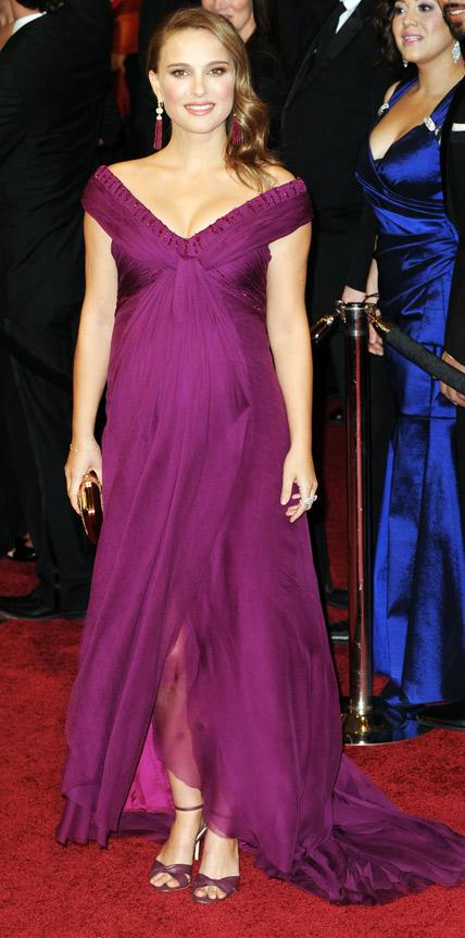 Full-length image of a woman in a floor-length purple dress with a deep v neck and short sleeves.